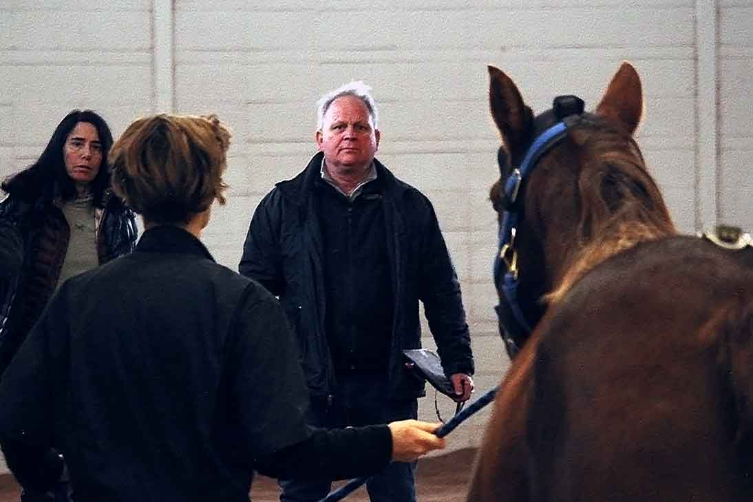 Dr. Kevin Keagan (right) and Dr. Nancy Loving (left) watch as the horse is trotted on a straightaway.